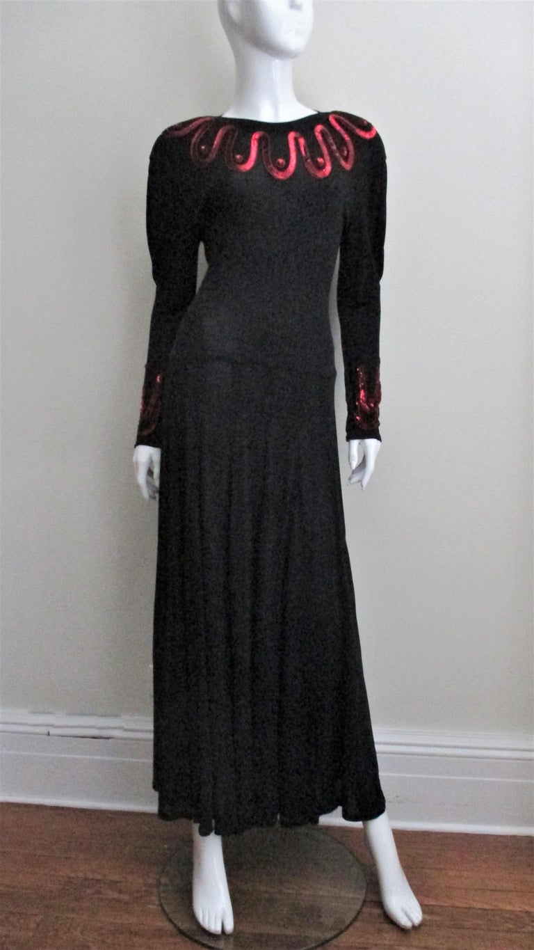 A beautiful rich black silk jersey dress from Jean Muir highlighted with waves of bright red sequins around the neck and cuffs.  It has padded shoulders, slight dolman sleeves with inverted pleating giving the upper arm adding some fullness.  The