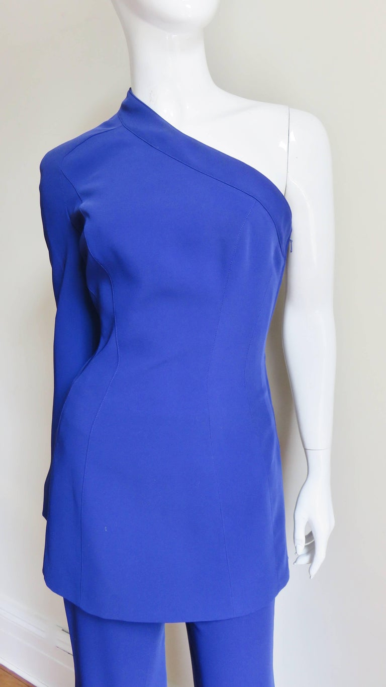 A clever and unique purple pant suit from Thierry Mugler.  It is comprised of a long jacket over full leg pants with a back zipper.  The tunic jacket has long bell sleeves, one which snaps into place and is removable. It has a side separating zipper