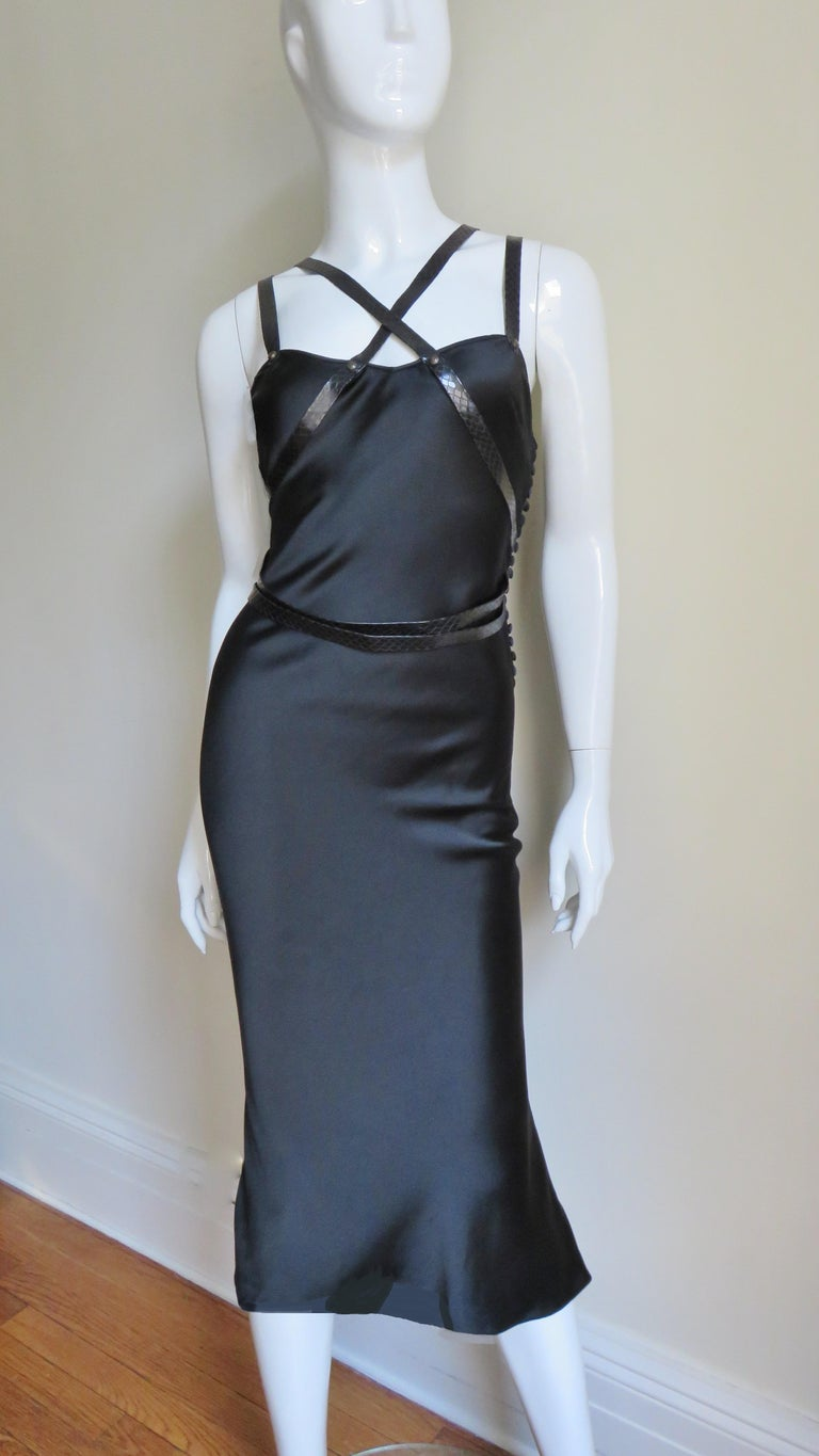 A fabulous black silk dress from Christian Dior. It is a fitted slip style dress adorned with 1/2