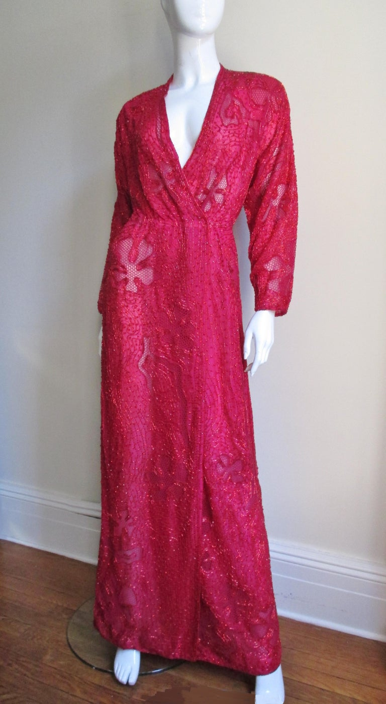 An amazingly detailed elegant red silk beaded wrap dress from Halston.  The floor length dress is covered in red glass tubular beads in an intricate pattern of flowers and abstract shapes.  The dress has a plunge neckline, slight dolman sleeves and
