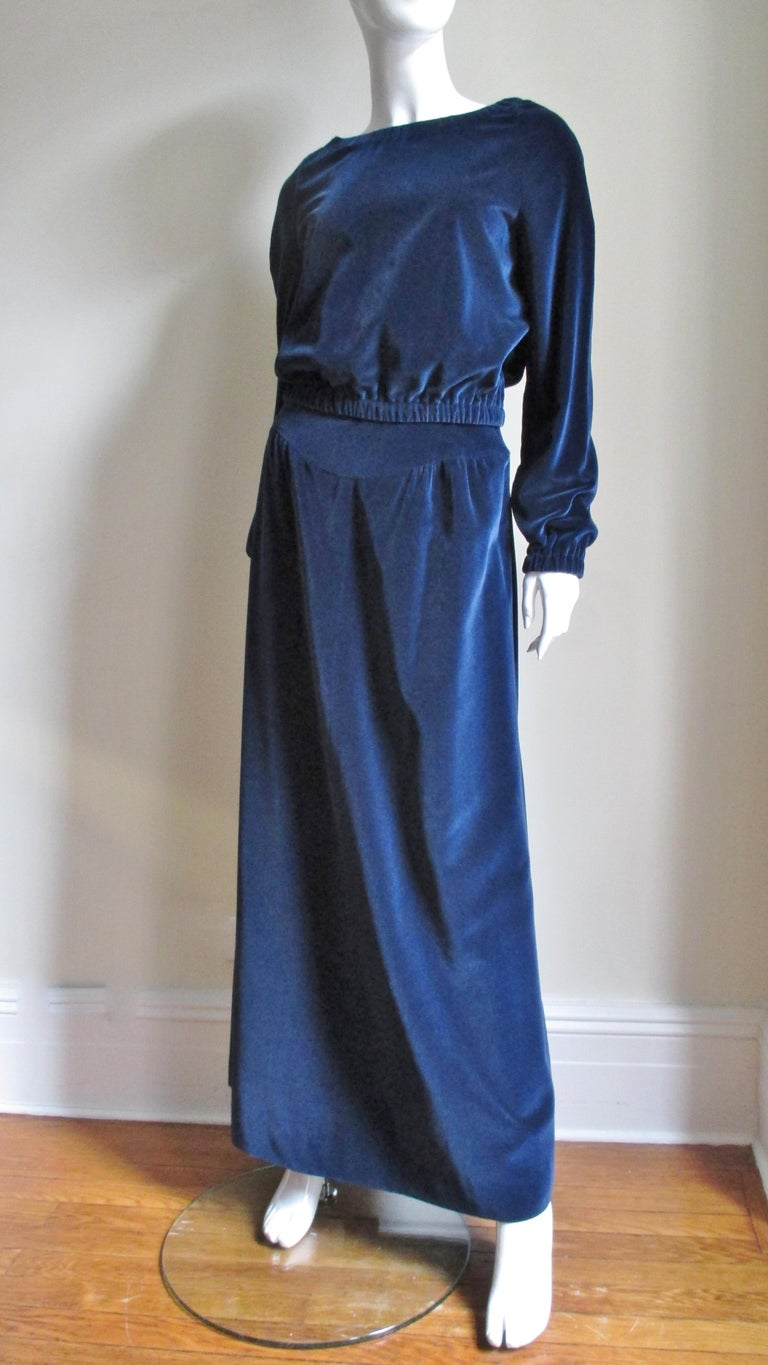 A fabulous 2 piece blue velvet set from Courreges.  The maxi skirt is gathered onto a curved front and back yoke. The bateau neck blouson top has stretch at raglan sleeve wrists, waist and neck and can be worn to reveal shoulders.  The top slips on