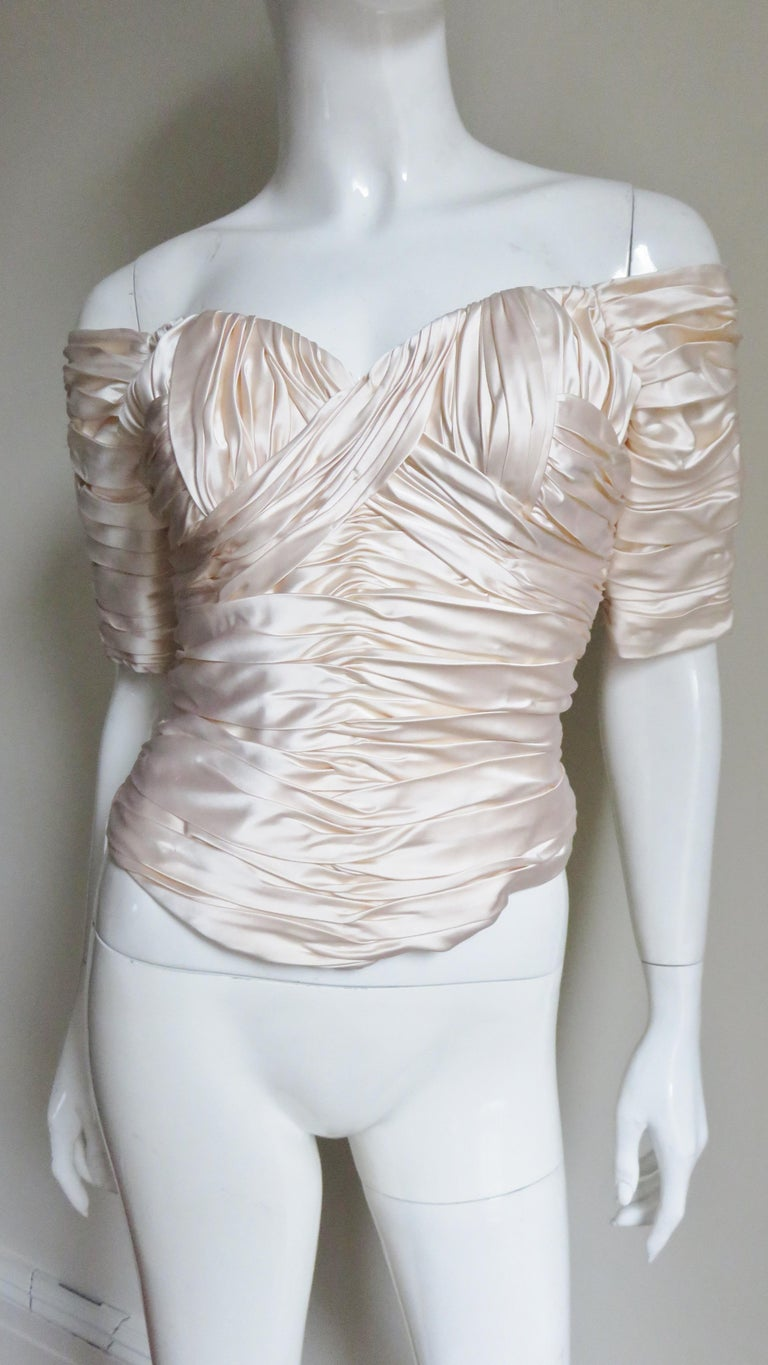 A beautiful off white silk corset top from Vicky Tiel.  It is worn off the shoulders with elbow length sleeves, a sweetheart cut neckline and ruching throughout in angles.  The front and back hem dip a bit longer in the center.  It has vertical