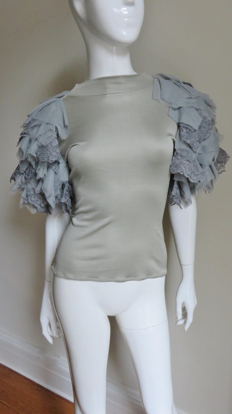 An incredible grey fine knit silk top from Alexander McQueen.  It has a crew neckline and elaborate grey net, tulle and lace appliqued layered sleeves. Unworn condition.  Fits sizes small, Medium.  Bust  35-38
