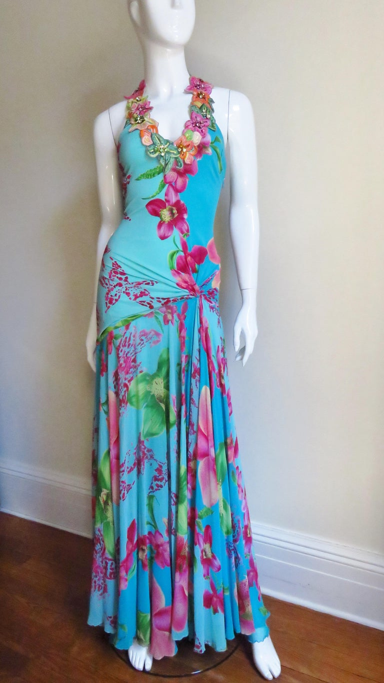 This is a gorgeous silk jersey and silk chiffon dress from Gianni Versace in pinks and greens flower pattern on a turquoise background.  It has a plunging neckline around which is adorned with intricately embroidered flowers decorated with colorful