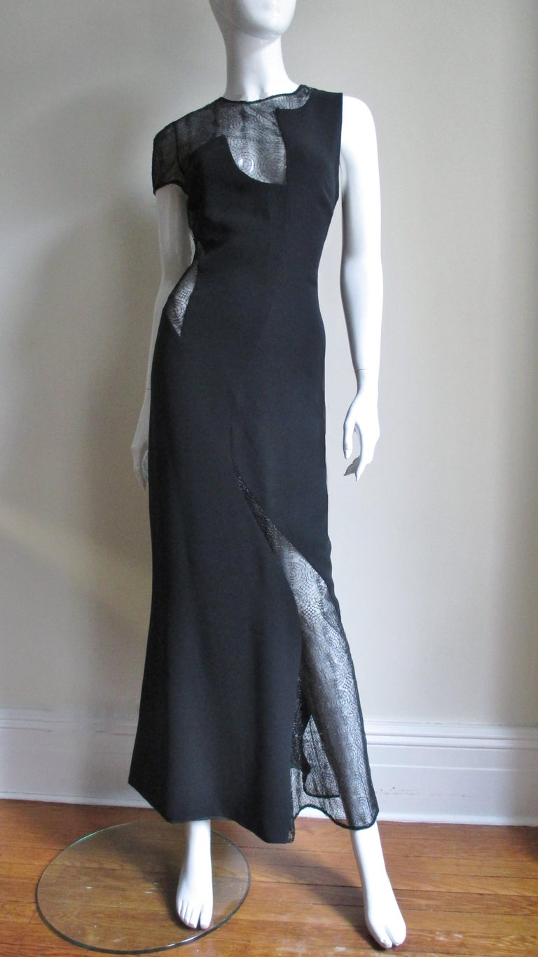 An amazing Gianni Versace Couture full length black silk and lace dress.  it has a scoop back and one short sleeve.  It is asymmetrically cut with web pattern lace covered cut outs at one side, leg, sleeve and decolletage. The dress skims the body