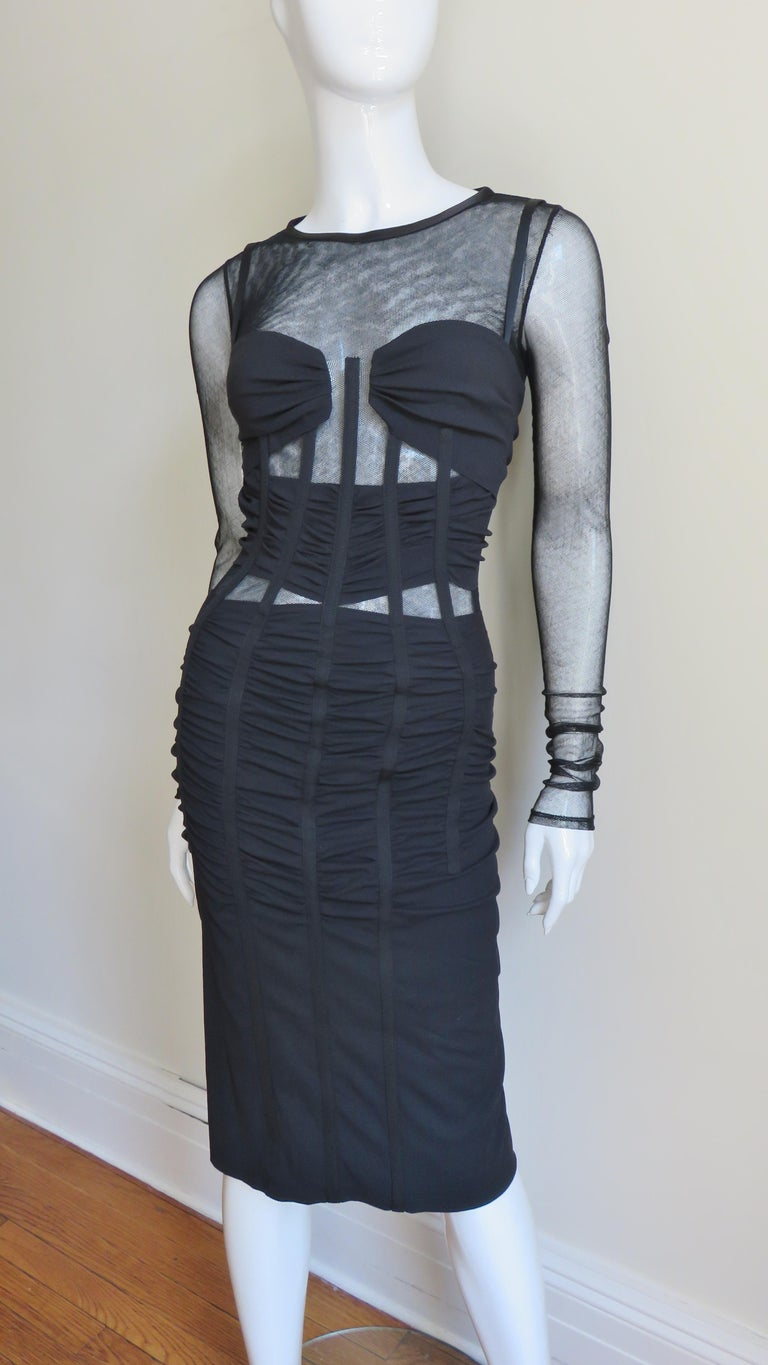 A fabulous sheer mesh and silk jersey dress from Dolce & Gabbana.  It is a fitted with long sleeves and ruched silk jersey over the mesh at the bust and at the waist. The bodice is vertically boned around it's circumference from the bust through