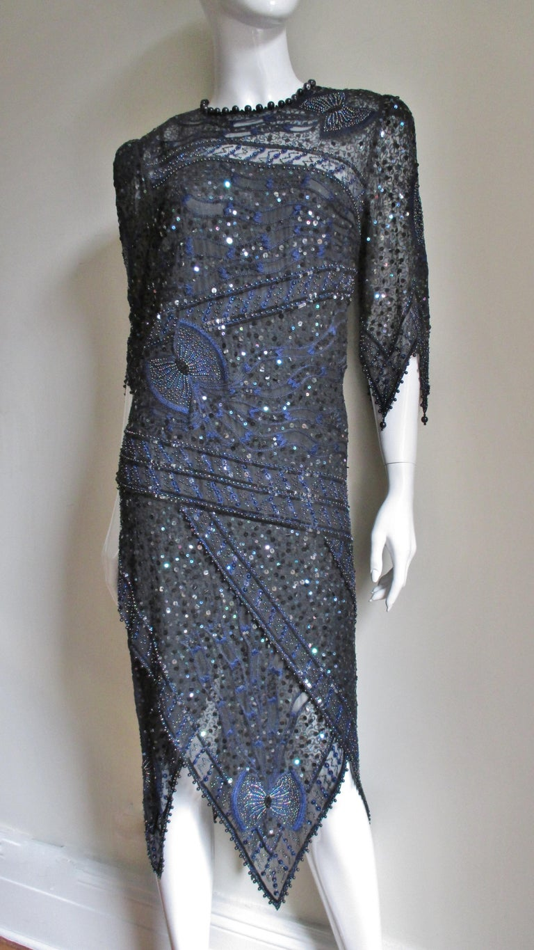 A gorgeous beaded, sequinned and embroidered dress from Zandra Rhodes.  It is made of semi sheer black silk embellished throughout with blue embroidery plus sequins and beads which shine in shades of blue and purple.  There are randomly placed