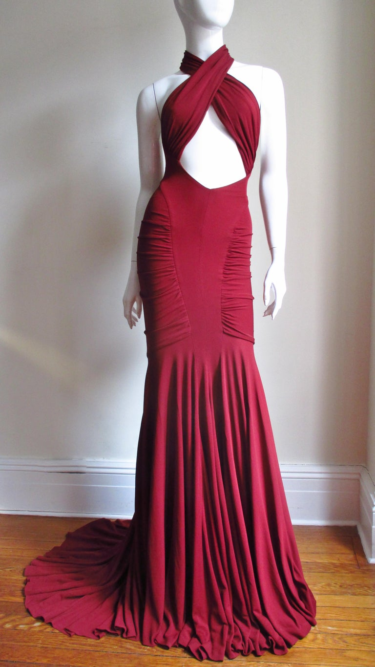 A stunning burgundy silk jersey gown by Herve Leger for the Guy Laroche 2004 Collection with the body conscious fit he is famous for. It has panels from the side waist crossing the bust, wrapping around the neck leaving a front cut out midriff and