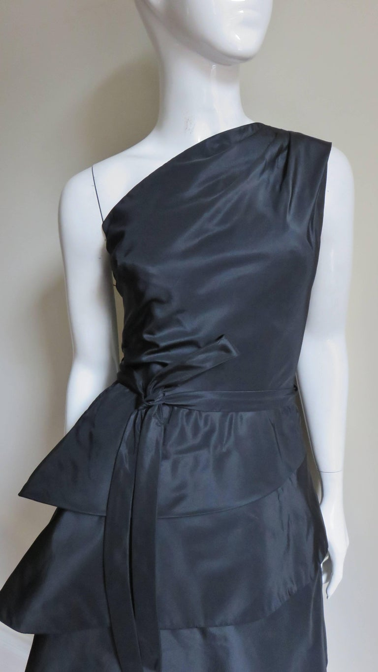 A stunning sculptural black silk dress from Werle, Beverly Hills.  It has a one shoulder fitted bodice with an inner boned corset. The skirt consists of a panel of fabric wrapping horizontally around 3 times forming a tiered bell shape flaring on