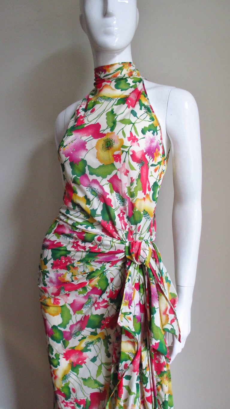 A stunning silk maxi dress in a yellow, red and green flower and leave pattern on an off white background from Valentino.  It has cut in shoulders and a stand up collar with a back self covered button and loop closure above a keyhole opening. One