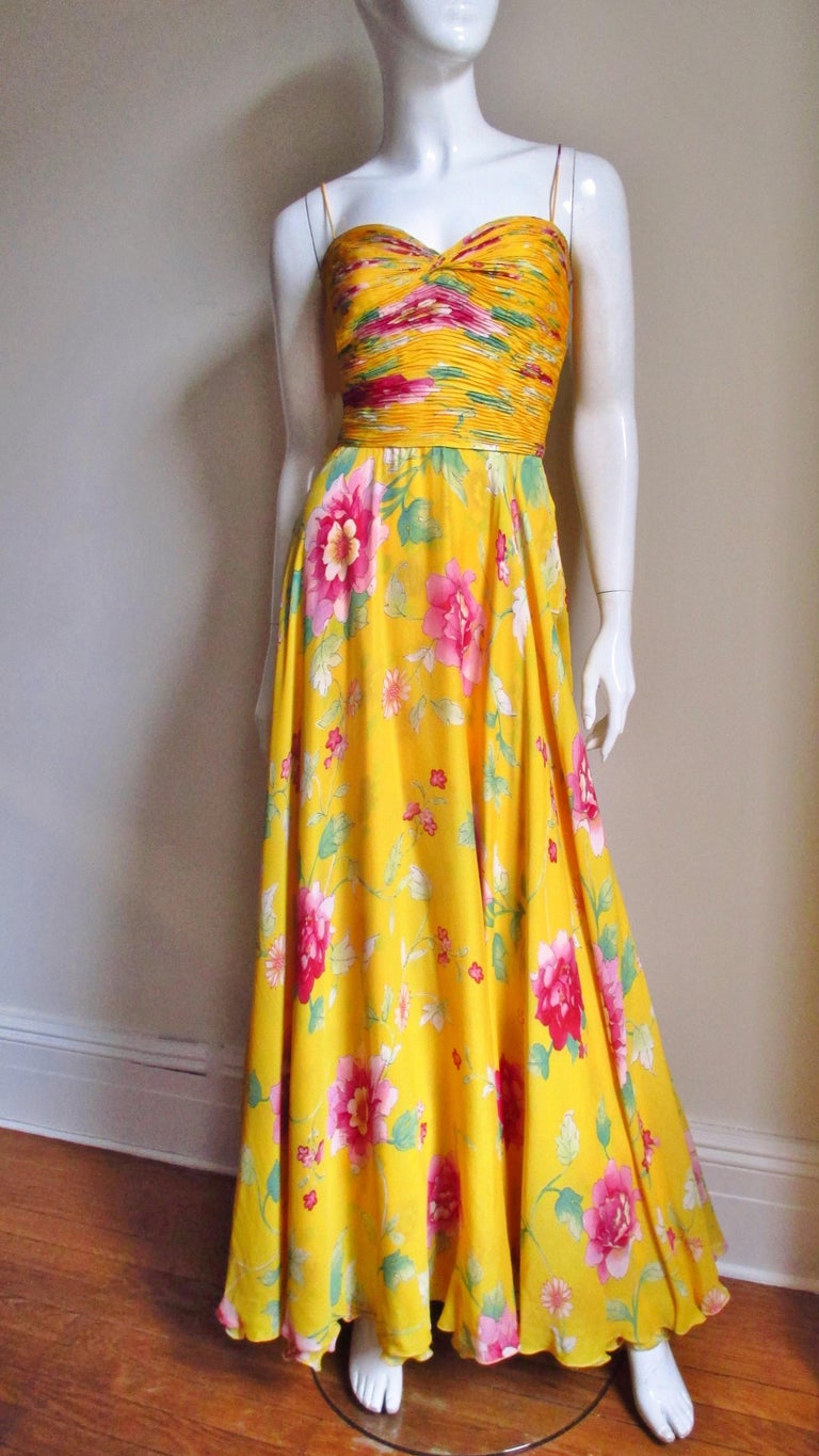 A beautiful marigold yellow silk dress from Valentino's 2006 Spring/ Summer Collection with a pink and green flower pattern.  The sweetheart bodice has spagehtti straps and is horizontally ruched front and back.  The skirt is simple flaring towards