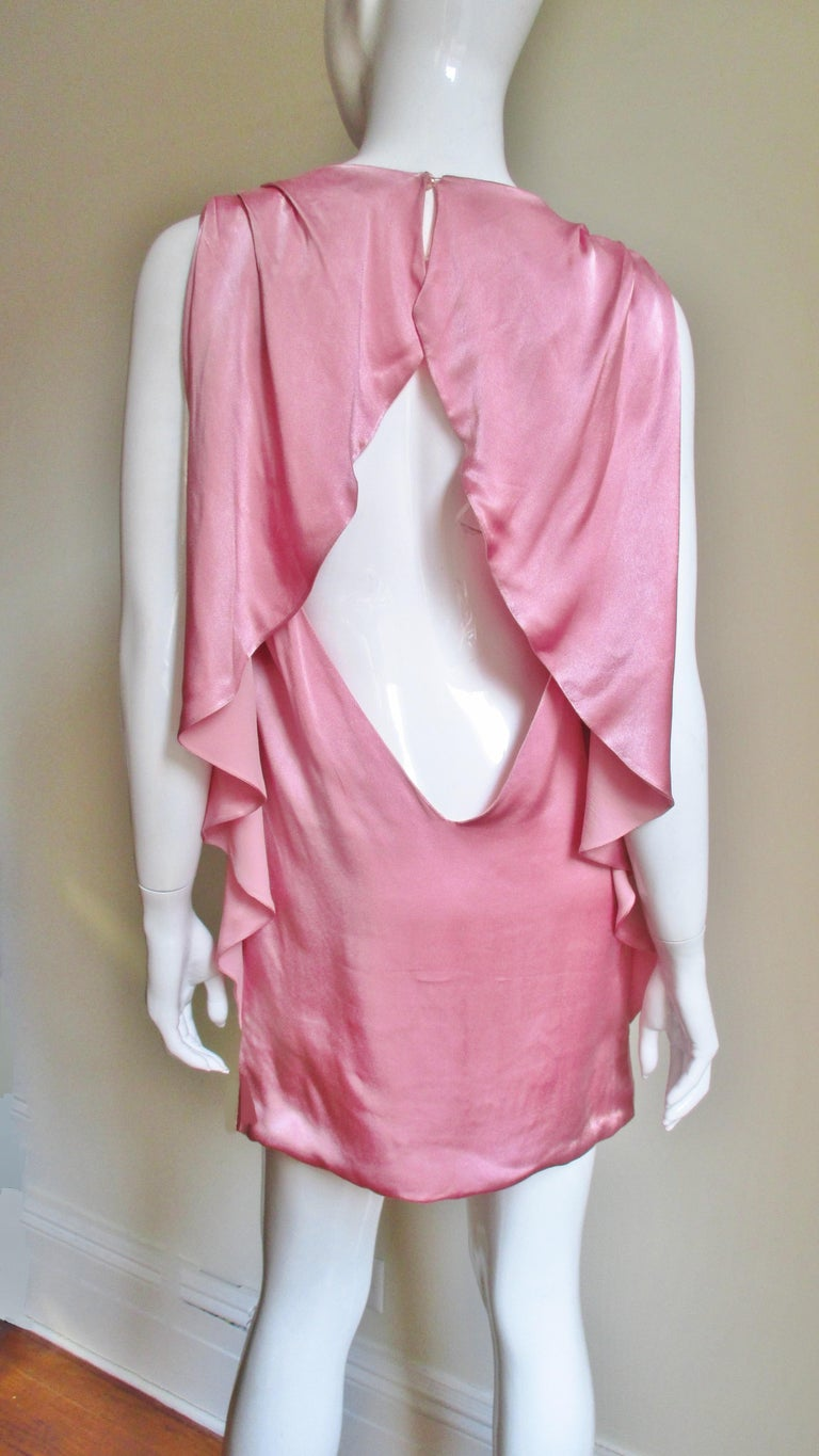 A beautiful dress in pink silk from Versace.  It is is a simple sleeveless shift from the front.  The back is exposed from the shoulders to low back with the exception of draping ruffles framing it across the shoulders and along the dress sides.  It