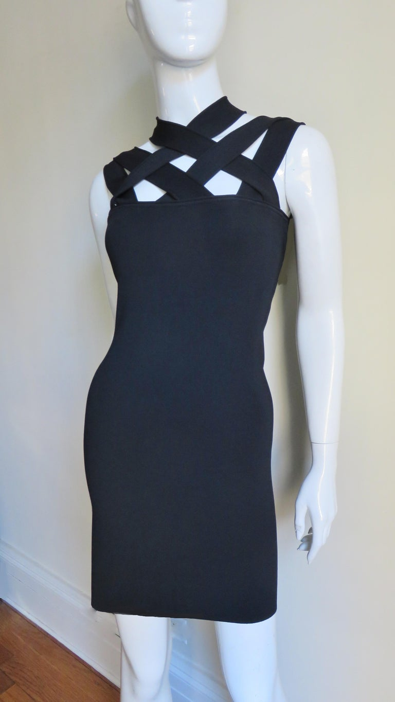 A great black bandage style dress from Givenchy.  It is made of stretch bandage fabric for a fitted silhouette.  It has criss crossing straps at the chest and upper back, is unlined and slips on over the head.    Fits sizes Extra Small, Small,