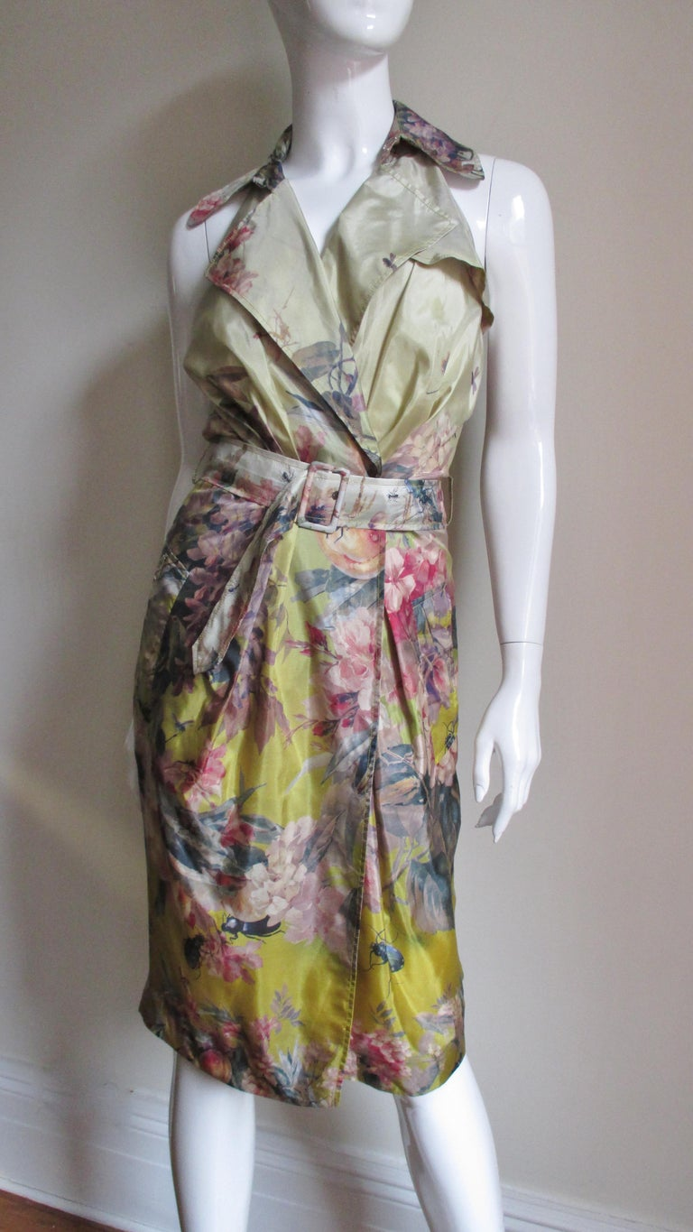 A great silk dress from Jean Paul Gaultier in a pattern of dragonflies, other insects and flowers in shades of green, gold, coral and pink on a yellow background.  It is wrap style with a matching self covered buckle belt and a yoke at the upper