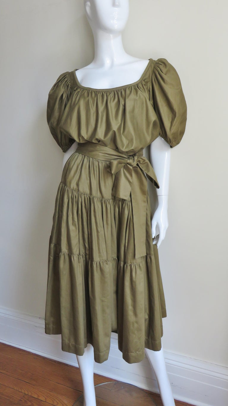 A fabulous 1960s top and skirt from YSL Rive Gauche in olive polished cotton.  The peasant style blouse has gathered puff sleeves and a wide gathered neckline.  The skirt consists of 3 gathered horizontal panels each wider than the other towards the
