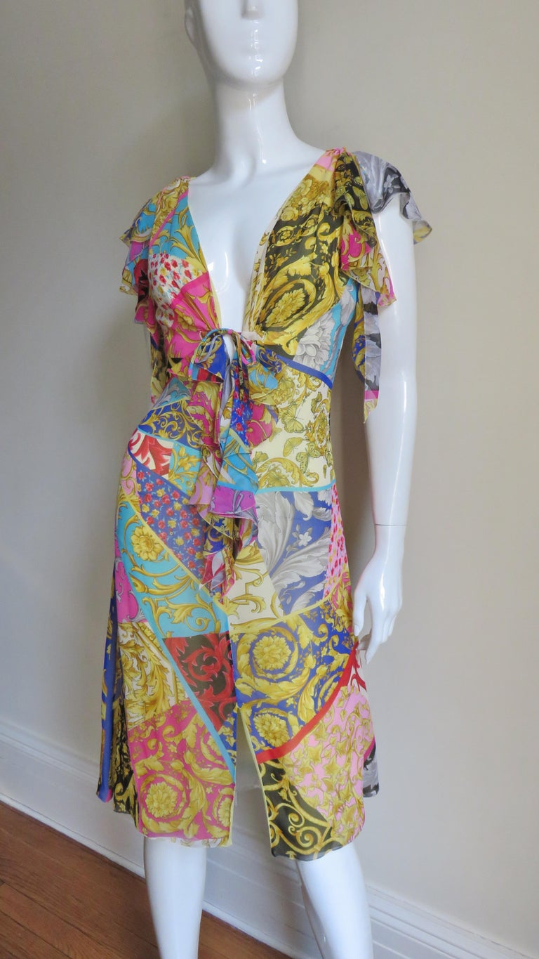 A compilation of some of Gianni Versace's most notable colorful pattern elements including scrolls, feathers, flowers in a beautiful silk dress.  It has a plunging neckline, ruffles draping around the shoulders and a center front slit in the skirt.