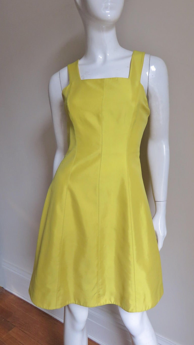 A beautiful vibrant yellow silk from Claude Montana. It has a square neckline, princess seaming for a great fit and an A line skirt.  The back straps meet a band mid level with a cutout beneath.  It has matching silk lining, matching back invisible
