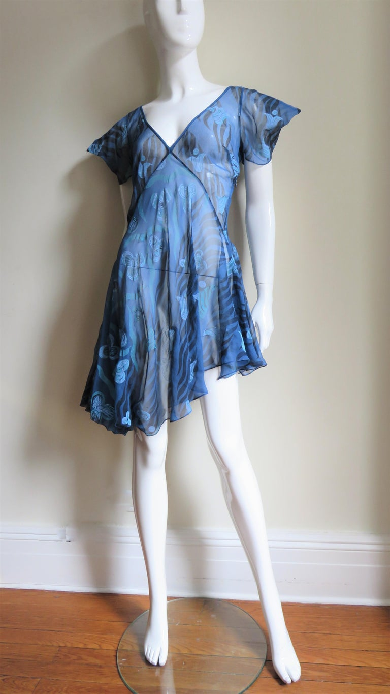 A beautiful dress in a blue sheer silk abstract flower print from Zandra Rhodes. It has a deep V neck and puff sleeves accentuated with points.  It is semi fitted through the waist and than flares in waves to the asymmetric hemline.  It is unlined