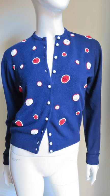 A beautiful beaded cashmere cardigan sweater from Elsa Schiaparelli in a cross between navy and royal blue.  The front is decorated with circles of different sizes in red glass seed beads outlined with white glass beads and the reverse with white