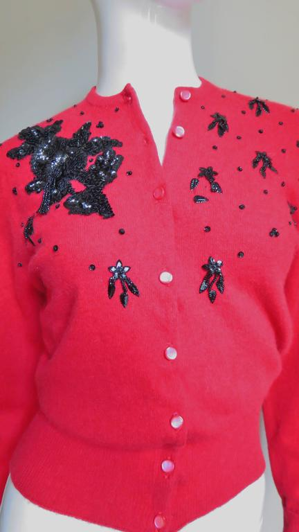 A beautiful rich red cashmere beaded cardigan sweater from Lyle & Scot.  It has long sleeves with ribbed neckline, fold back cuffs and hem.  The front right chest near the shoulder is adorned with black glass seed beads and sequins in an abstract