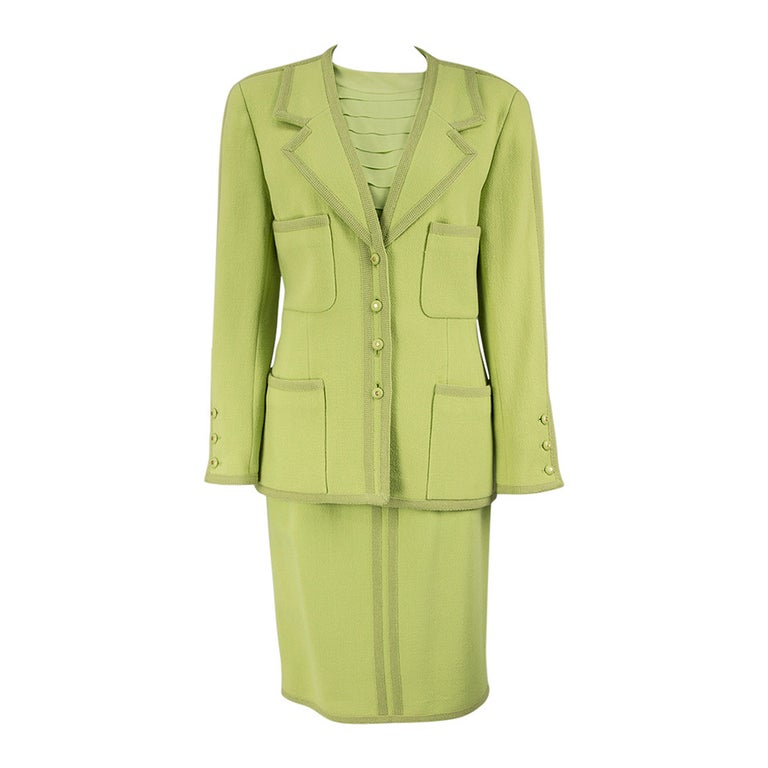 This Chic and Timeless suit features a Jacket Blazer single breasted buttoned front and four pockets, featuring grosgrain trim, buttons are decorated with the Chanel logo. The straight skirt has grosgrain trim, a back zipper and band, the Crepe de