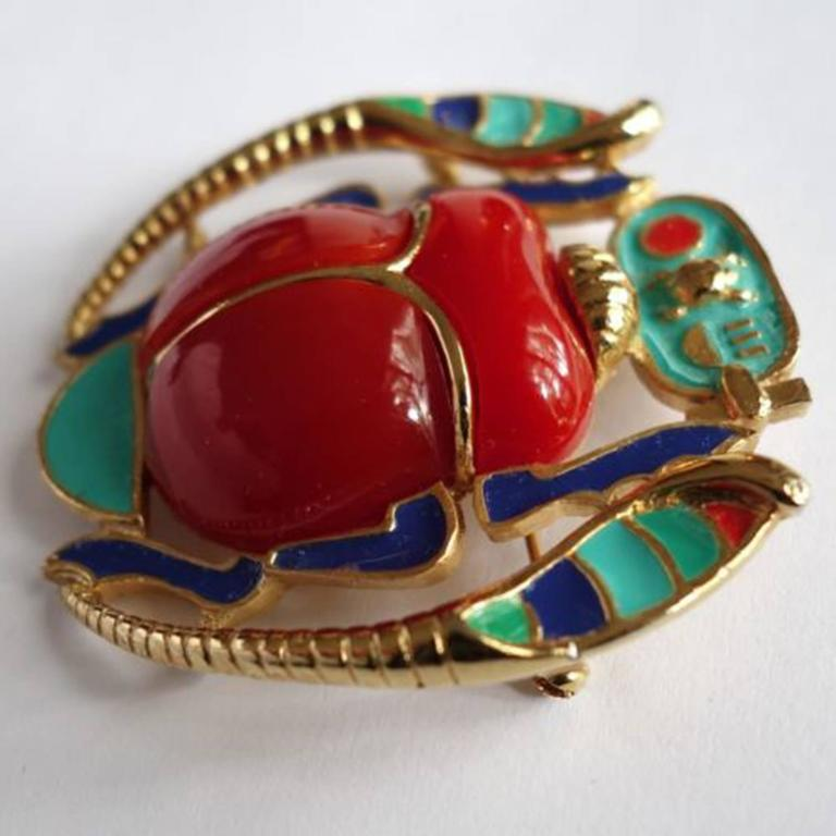 """Featuring a vibrant red acrylic and enamel Scarab flanked by enamel accented stylized Serpents.  It measures approx 2.25"""" x 2.25""""; signed: HATTIE CARNEGIE in oval cartouche on the underside. C1960s Chic and Timeless… Illuminating your Look"""