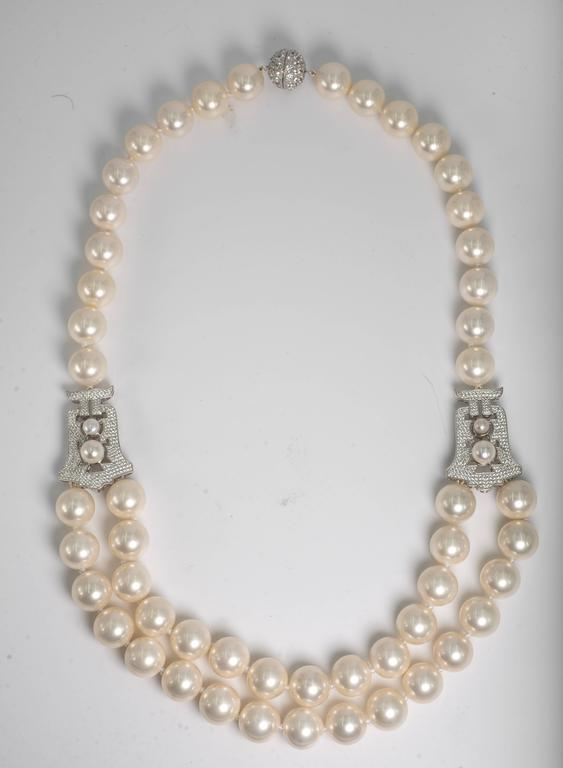 Elegant classic Audrey Hepburn Style one row14 mm pearls  at the back, side pave cubic zirconia sterling motifs suspending two rows of 14mm pearls for the front. The Art Deco style pave motifs  are 1 1/4 inches. Total length 24 inches with a pave