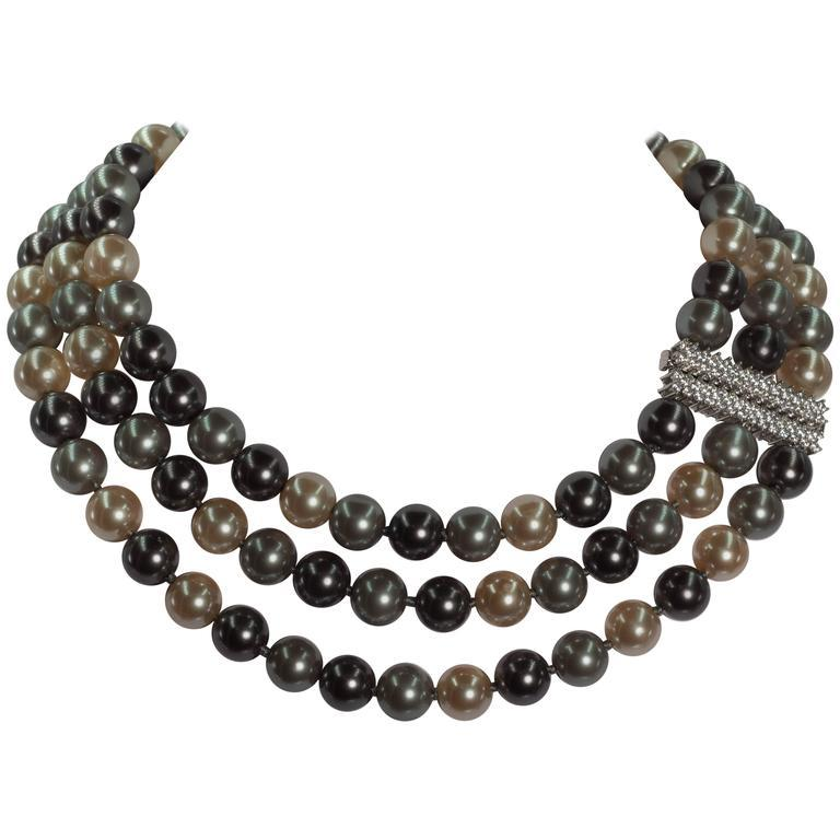 Three strands of 12mm faux Tahitian pearls interspersed silk knotted and strung attached to a cubic zirconia sterling fine jewelled clasp which can be worn as shown on the side or the back of the neck. The inner row is 18'', the second row is 20''