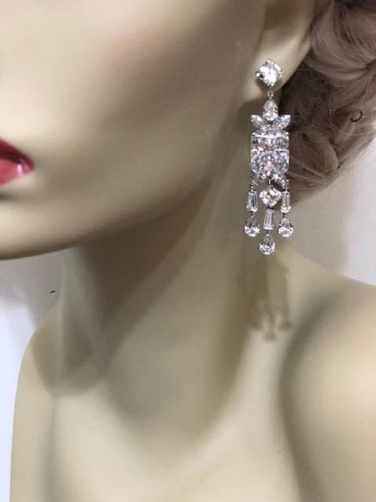 A pair of stunning faux synthetic diamond white cubic zirconia sterling earrings. The intense realness of the stones are equivalent to 8 carats surrounded by bright white cubic zircons all set like the finest real diamond jewelry. Set in rhodium