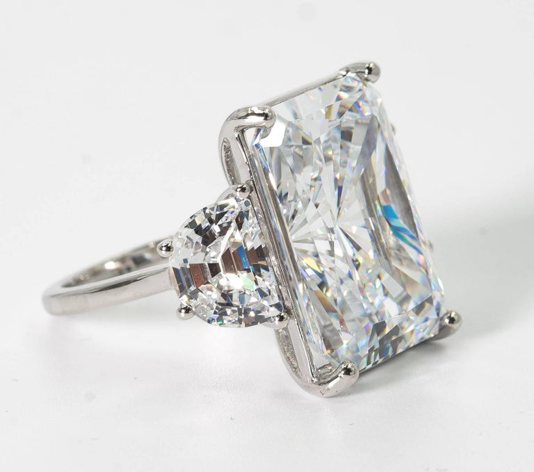 Magnificent f synthetic white 25 carat Radiant Cut Cubic Zirconia ring set with classic half moons side stones. The radiant cut cubic zircon is a wonderful high quality white color that reflects and sparkles exactly like a gem! Measures 7/8th inch