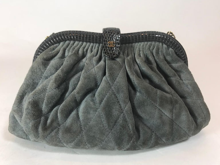 Dark gray quilted suede. Gold-tone hardware. Python trimmed detail. Top closure lock featuring small
