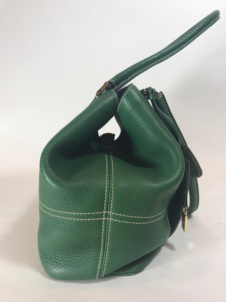 Green leather. Gold-tone hardware. Snap closure at top. Ivory contrast stitching. Dual rolled shoulder straps. Dual pockets at exterior; one with zip closure. Protective feet at base. Canvas lining with four interior pockets; one with zip closure