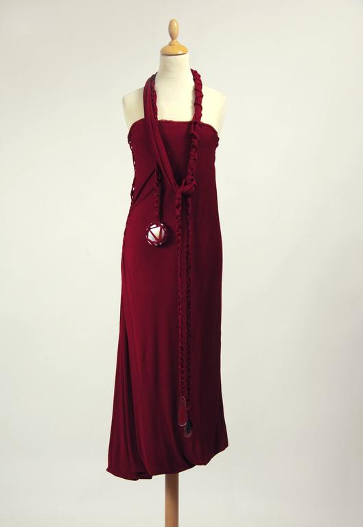This gorgeous Jean Paul Gaultier dress in in a dark magenta red jersey silk fabric. It include an amazing shoulder straps or sash belt with plastic details and has side zip closure. It's fully crepe pleateds silk fabric