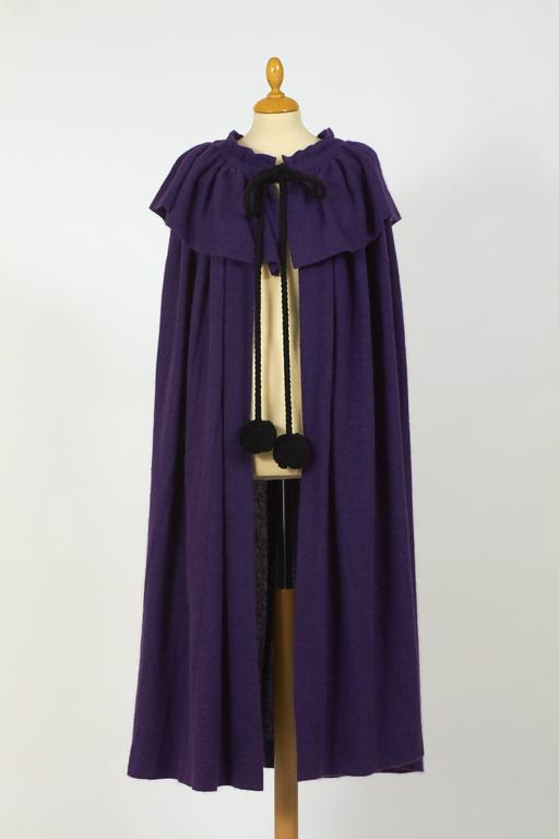 This gorgeous 1970s Yves Saint Laurent Rive Gauche cape cloack is in a purple angora wool fabric and has flounce collar and black pom pom tie cord closure. 