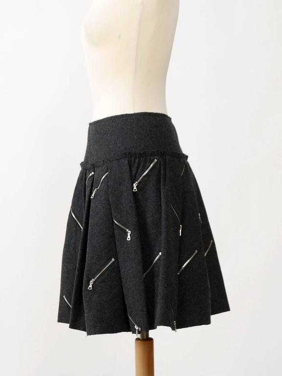 This gorgeous Marc Jacobs mini skirt is in a gray soft woolen fabric. It's full pleateds and has multi zipper details and back zip closure. It's fully black silk satin lined.