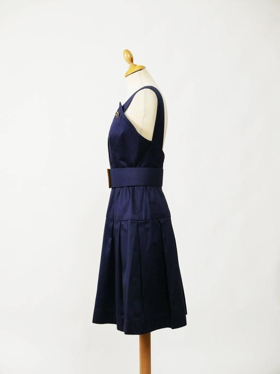This lovely Chanel sleeveless dress is made with a navy blue cotton fabric. It has back zipper and is fully lined. It has pleateds skirt and buttons marked Chanel. It's included the belt with logo buckle.  Very good vintage condition   Label: