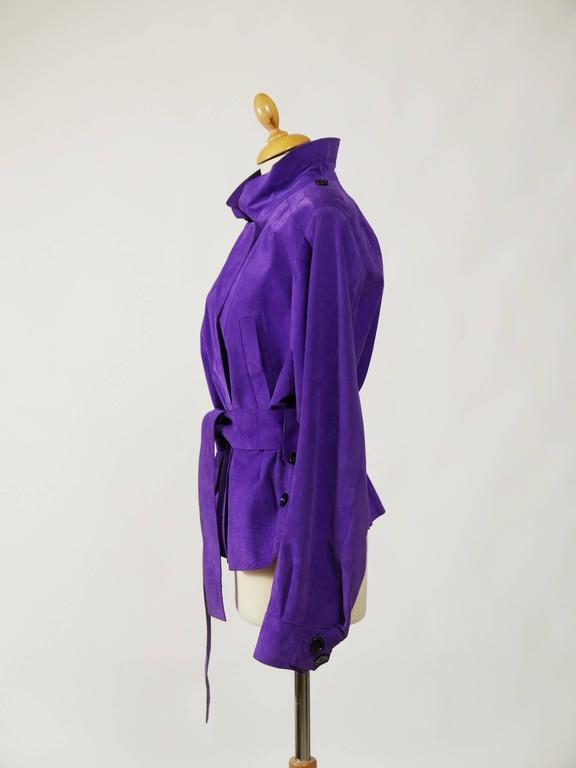 This lovely Yves Saint Laurent jacket is in a purple suede soft leather. It has assymetyric buttons closure, belt and side pockets.