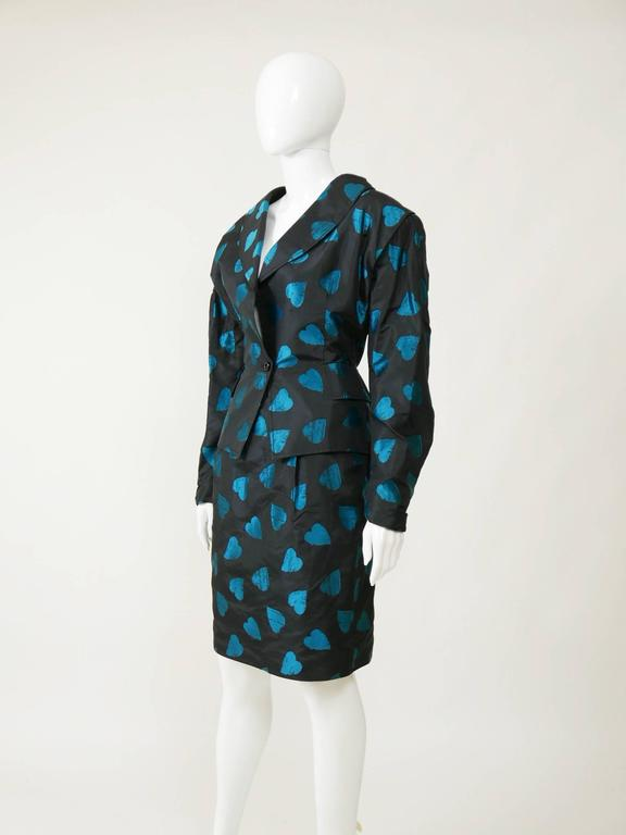 This amazing, sexy and feminine set of Umanuel Ungaro from the late 1980s has a typical oversize 80s style. It's in black silk taffeta with turquoise hearts print. The peplum jacket has padded shoulders and one button closure, faux frontal pockets