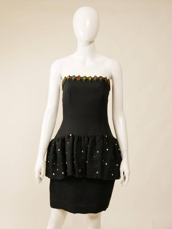 This amazing Saint Laurent 1980s cocktail dress is in a black silk fabric with beadeds and rhinestones details. The strapless top is straight across and has ruffled skirt over pencil skirt and is satin lined. 