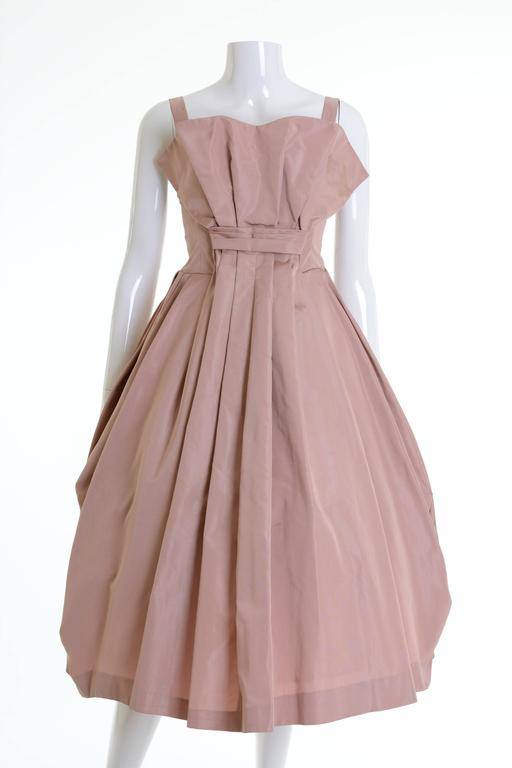 This amazing 1950s cocktail dress is in a powder pink silk taffeta fabric. It has full pleateds circle skirt and back zip closure. The petticoat is not included.  Very good vintage condition   Label: N/A Fabric: silk taffeta Color: powder