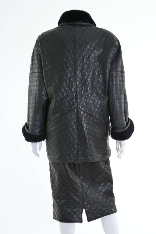 This awesome Gianni Versace suit dress is in a black soft quilted leather and sheepskin. The jacket has oversize line, dolman sleeves, padded shoulder and asymmetric closure, two side pockets and is lined with black warm woolen fabric. The skirt has