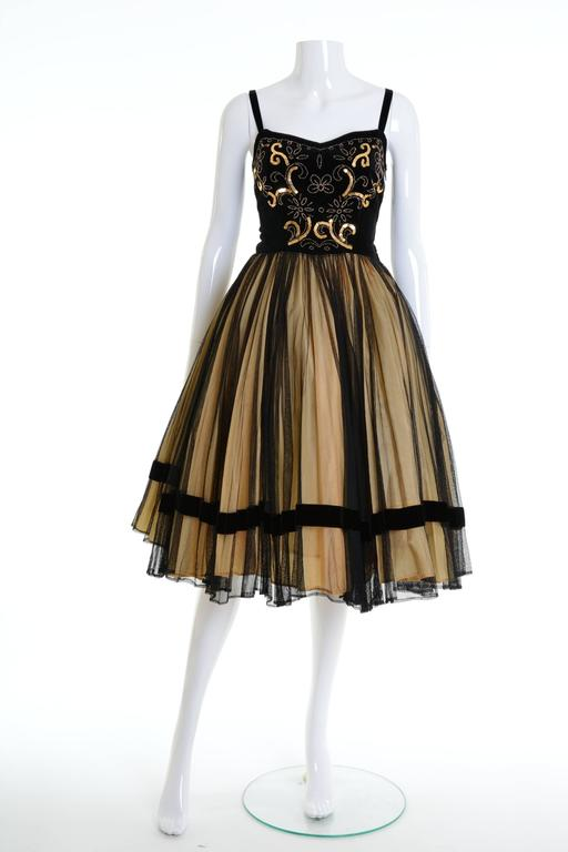 This gorgeous 1950s dress is in a black velvet and tulle fabric with amazing golden sequins and beadeds embroidered. It has a full circle skirt and side zip closure. It's fully lined.   Good vintage condition   Label: N/A Fabric: silk/nylon Color:
