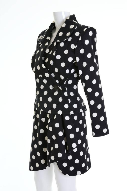 This lovely early 1990s Yves Saint Laurent Rive Gauche suit dress is in a black pique cotton fabric with white polka dots print. It has fitted jacket with padded shoulders and wrap mini skirt. It's fully satin lined.  Excellent vintage