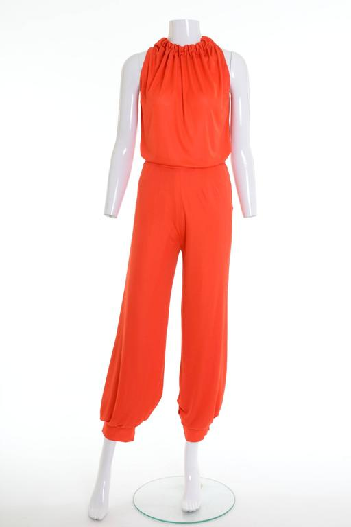 1960s 1970s Deadstock Gio Caré pants suit in a orange rayon fabric, sleeveless top with drawstring, fully lined button-hem joggers with side zip closure.  Condition: never worn with tag  Label: Gio Caré Fabric: rayon Color: