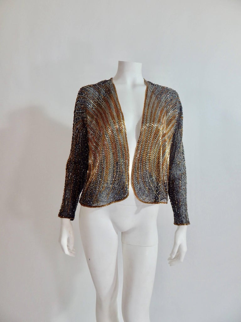 Fabulous 1970s / 1980s Vintage Halston Beaded Cover or Jacket. Sheer black with black, silver and gold beading. Bead work design in the style of disco and art deco. Versitale with formal gown or dress up denim. Tag reads size 4.