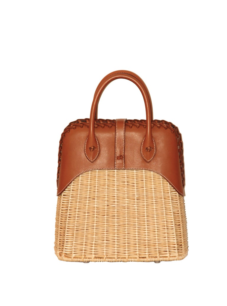This exquisite and amazing Bolide Picnic bag is made of Barenia leather and woven wicker. The front leather strap closes with with a Clou de Selle button and a braided leather piece finishes the top of the bag. The double handles are decorated with