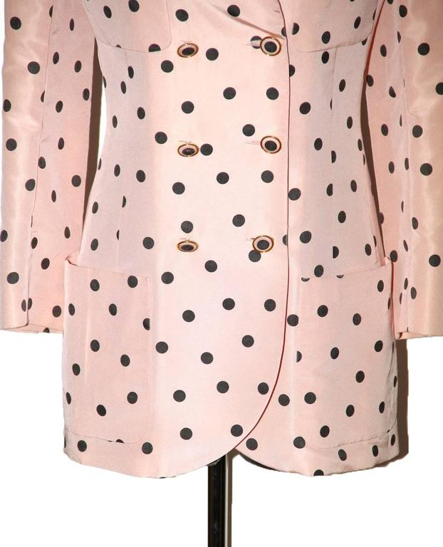 Elegant and timeless Chanel pink and black polka dot jacket. It features a black velvet collar, 6 front buttons and 4 pockets. The blazer is fully lined of tonal pink silk with embroidered CC.  Tags have been removed.  It sizes as a FR 36/38.