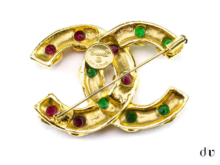 Make a statement in this edgy Chanel brooch! This brooch features green and red gripoix details amongst the interlocking gold 'CC' logo. Pins at the back. Made in France.  Includes: Box  Measurements: 2.25
