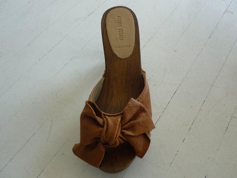 """Nice solid wooden base and heels with bowed and stud embellishments. These sandals are in excellent condition.  3"""" heels. Made in Italy"""