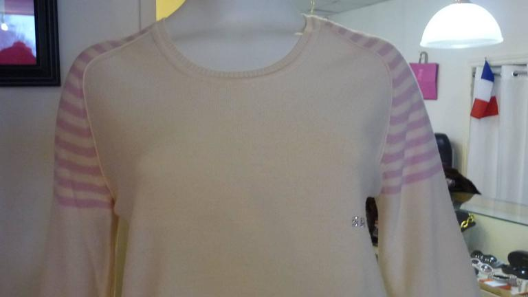Never worn this is a beautiful sweater with great attention to detail. The back is slightly longer than the front; there are side vents as well as slits at bottom of sleeves.  There is also the SR sparkly initials on the front.